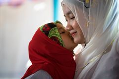 An Giang, Vietnam - Sep 6, 2016: Vietnamese muslim girl wearing traditional red dress playing with her sister in a champa village,. Khanh Hoan district, South Stock Photography