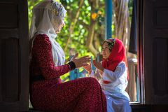 An Giang, Vietnam - Sep 6, 2016: Vietnamese muslim girl wearing traditional red dress playing with her sister in a champa village,. Khanh Hoan district, South Stock Photos