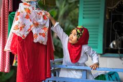 An Giang, Vietnam - Sep 6, 2016: Vietnamese muslim little girl hanging clothes for outdoor drying in a champa village, Khanh Hoan. District, South Vietnam Stock Images