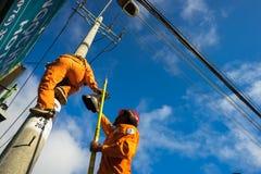An Giang, Vietnam - 6 settembre 2016: Salita asiatica dell'elettricista alta sul palo per riparare sistema elettrico nel distrett Immagine Stock