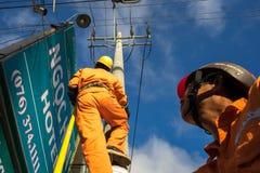 An Giang, Vietname - 6 de setembro de 2016: Escalada asiática do eletricista alta no polo para reparar o sistema bonde no distrit Imagem de Stock