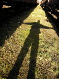 A giant. A shadow of a person standing on the grass between two trains Royalty Free Stock Photography