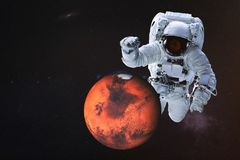 Giant astronaut near Mars planet. Of Solar system. Science fiction wallpaper. Elements of the image are furnished by NASA royalty free stock photography