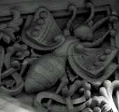 Giant bee on the corner. Shot in black and white  detail on the sculpture on the facade of this historic building representing some  characters / animals / Stock Photos