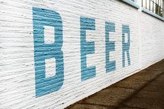 Giant Beer Sign in Blue Text on a White Brick Wall. A giant blue letter painted sign spelling BEER on a white brick wall next to a sidewalk stock photo