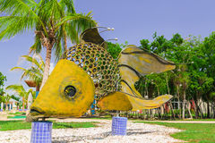 Giant big, decorative beutiful fish made of metal  shits and horshoe parts, standing on ceramic tile posts in cozy tropical garden Stock Photos