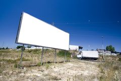 Giant billboard in public road. Giant billboard near a public road with cars passing by Royalty Free Stock Photo