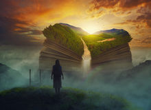 Giant book. A woman hikes to a giant book with waterfall stock photography