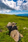 Giant boulders on grassy slopes of Polonina Runa. Beautiful summer scenery in Carpathian mountains with gorgeous cloudscape Royalty Free Stock Photography