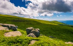 Giant boulders on grassy slopes of Polonina Runa. Beautiful summer scenery in Carpathian mountains with gorgeous cloudscape Royalty Free Stock Photo