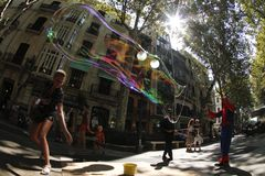 Giant bubbles on the street. A disguised man make soap giant bubbles in the streets of palma de Mallorca as a way to get some cash from tourist and surprised Stock Photo