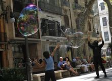Giant bubbles on the street. A disguised man make soap giant bubbles in the streets of palma de Mallorca as a way to get some cash from tourist and surprised Stock Photos