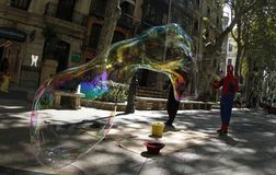 Giant bubbles on the street. A disguised man make soap giant bubbles in the streets of palma de Mallorca as a way to get some cash from tourist and surprised Royalty Free Stock Images