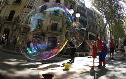 Giant bubbles on the street. A Young girl make soap giant bubbles in the streets of palma de Mallorca helped by a disguised jobless person as a way to get some Stock Photos