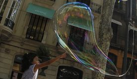 Giant bubbles on the street. A Young girl touches soap giant bubbles in the streets of palma de Mallorca made by a jobless person as a way to get some cash from Stock Image