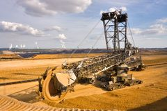Giant bucket wheel excavator. Taking away the layers of ground before digging the brown coal. Largest open pit lignite mine in Europe. Power stations at horizon Royalty Free Stock Photo
