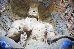 Giant Buddha. Colorful wall in a Buddha cave in China. The statue is giant standing very high Royalty Free Stock Images