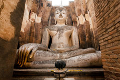Giant Buddha sitting in calmness between ancient walls of Wat Si Chum Stock Images