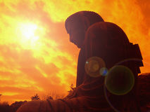 Giant Buddha under the sun. Giant bronze statue of Japanese Buddha under the sun with lens flare and orange filter under dramatic cloudy sky Royalty Free Stock Photo