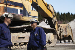 Bulldozers, trucks and worker in action Royalty Free Stock Photos