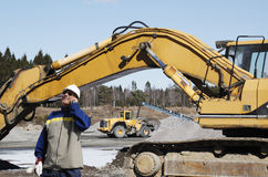 Bulldozers, trucks and worker in action Royalty Free Stock Photo