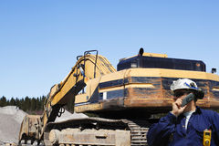 Bulldozers, trucks and worker in action Stock Photo