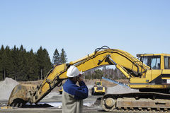 Bulldozers, trucks and workers in action Stock Images