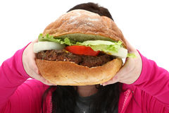 Giant Burger. Super huge giant burger and teen girl trying to eat it stock photography