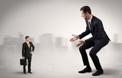Giant businessman is  afraid of small executor. Giant businessman being afraid of small serious executor with suitcase Stock Photos