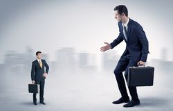 Giant businessman is  afraid of small executor. Giant businessman being afraid of small serious executor with suitcase Stock Photo