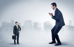 Giant businessman is  afraid of small executor. Giant businessman being afraid of small serious executor with suitcase Stock Images
