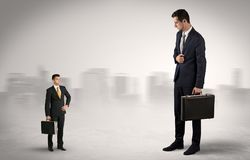 Giant businessman is  afraid of small executor. Giant businessman being afraid of small serious executor with suitcasen Royalty Free Stock Image