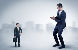 Giant businessman is  afraid of small executor. Giant businessman being afraid of small serious executor with suitcasen Stock Photo