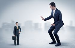 Giant businessman is  afraid of small executor. Giant businessman being afraid of small serious executor with suitcasen Stock Images