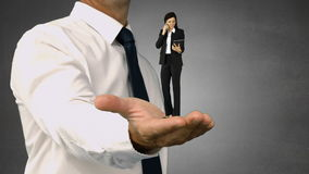 Giant businessman holding a businesswoman stock video