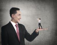 Giant businessman holding little man yelling with megaphone. Giant business men holding little men yelling with megaphone. Politic in business Stock Photo