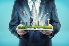 A giant businessman holds an open book that also holds a tiny businessman standing on a field near skyscrapers. stock image