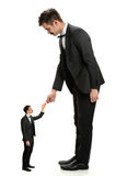 Giant Businessman Shaking Hands With Small Man Royalty Free Stock Images