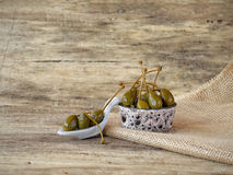 Giant capers in a bowl with spoon and placed on wo. Big fresh organic capers in a bowl placed on a piece of jute Royalty Free Stock Images