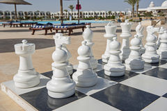 Giant chess board game in tropical resort. Closeup of playing pieces on giant chess boards game in tropical hotel resort with swimming pool Stock Photo