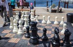 Giant chess game in the waterfront, Cape Town. A father and his daughter playing chess in the waterfront in Cape Town, South Africa Stock Image