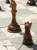 Giant chess pieces stand on outdoor chess-board Royalty Free Stock Image