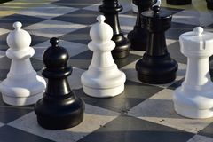 Giant chessboard with some pieces. Giant outdoor chessboard with some pieces casting long shadows in late evening light Stock Photos