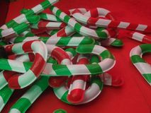 Giant Christmas candy cane lollipop decorations. Against a red background royalty free stock images