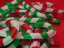 Giant Christmas candy cane lollipop decorations. Against a red background stock photography