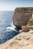 Giant Cliffs - Migra l-Ferha, Malta, Europe. Waves smash against massive cliffs, towering above the blue mediterranean sea Royalty Free Stock Image