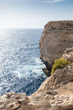 Giant Cliffs - Migra l-Ferha, Malta, Europe. Waves smash against massive cliffs, towering above the blue mediterranean sea Stock Photography