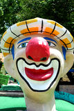 Giant clown head - miniature golf. Miniature golf courses challenge golfers at each hole with hazards like this giant clown head with big red nose Stock Photos