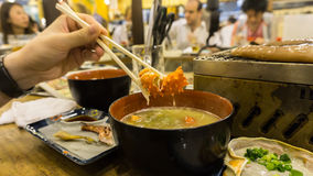 Giant crab legs soup holding by a chopstick. In a restaurant Stock Images
