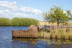 Giant cradle in Kinderdijk, Holland. A giant baby cradle on a historical water channel in Kinderdijk, Holland royalty free stock images